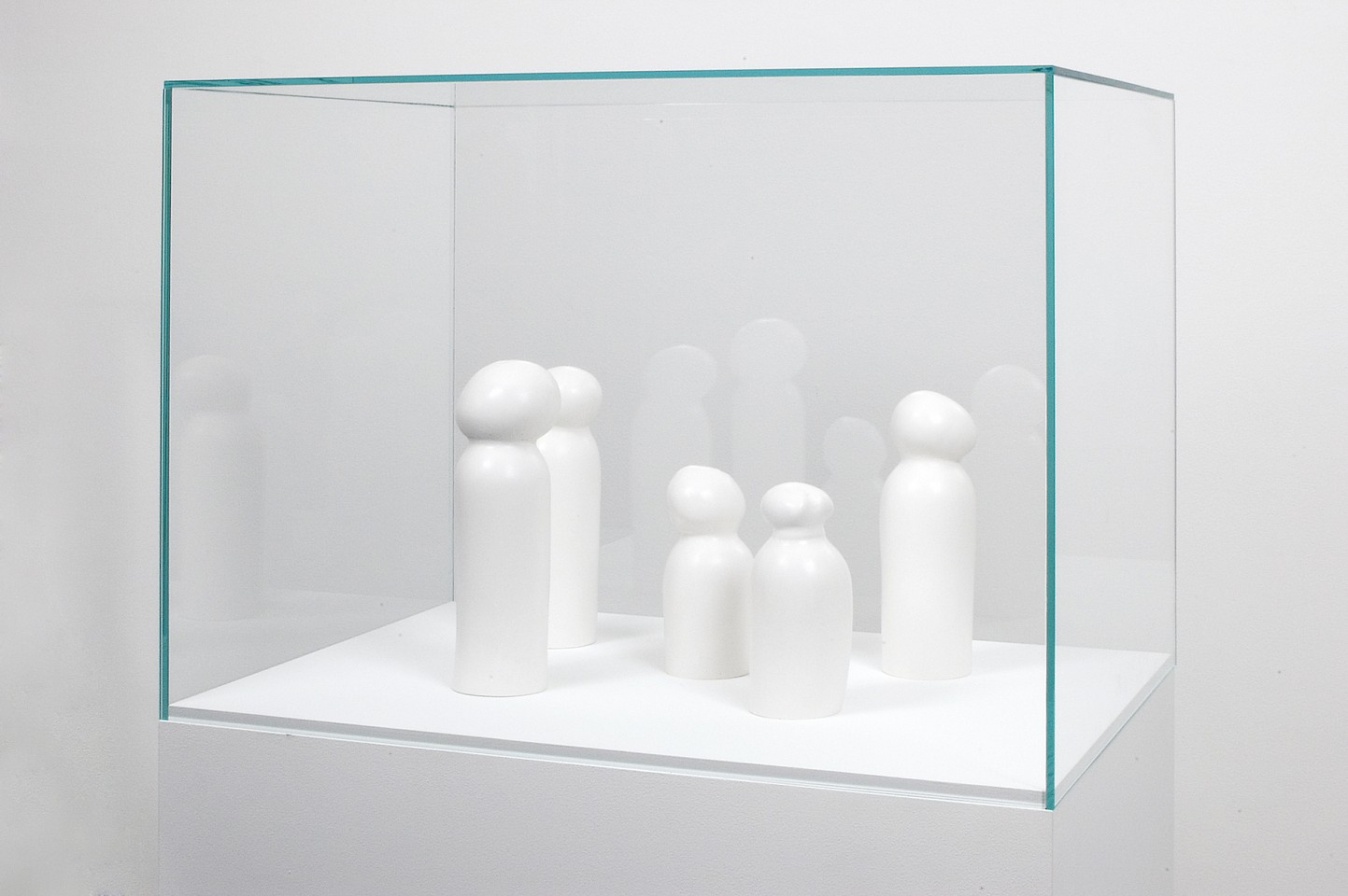 Victor Grippo ,   Anónimos  ,  1998-2001     painted plaster in five parts, painted wooden base, vitrine and text     overall: 60 3/4 x 28 x 20 in/154 x 70 x 50 cm 