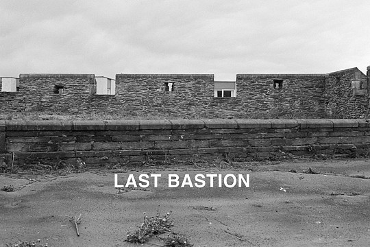 Willie Doherty ,   Last Bastion  ,  1992     black and white photograph with text mounted on aluminum     48 x 72 in/122x 183 cm     WID-92-PH-123