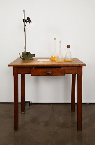 Victor Grippo ,   Mesa escrita  ,  2001     wooden table, lamp, glass bottles with three states of material, pencil on paper and dried rose      58 x 31 3/8 x 23 in/147 x 79.5 x 58.5 cm      VG-01-SC-032