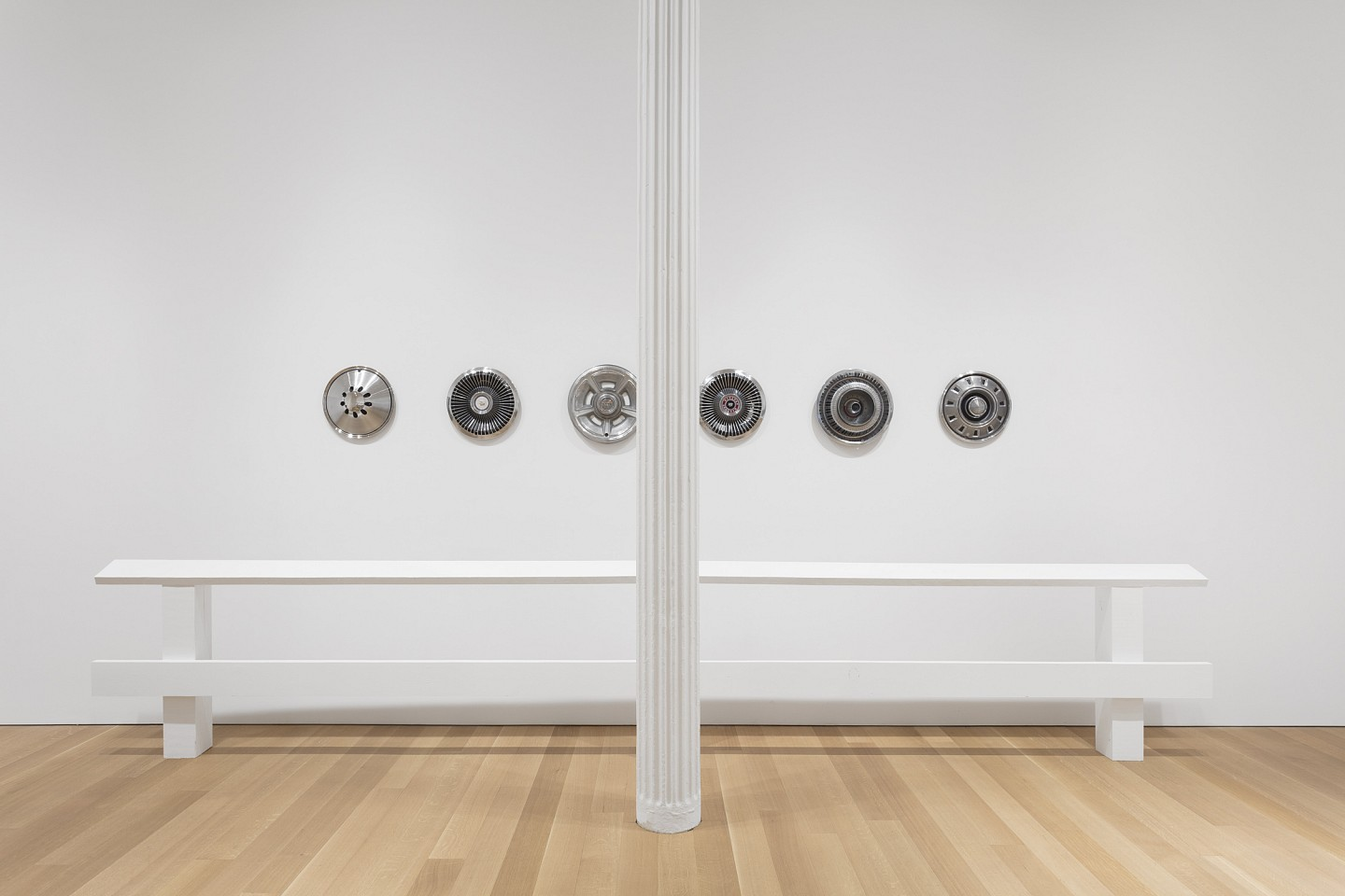 Rita McBride ,   Guide Rails with Hubcaps  ,  2017     wood, latex and 6 vintage hubcaps     installed dims: 70 3/8 x 193 x 20 in/178.7 x 490 x 50.8 cm     RMC-17-SC-434